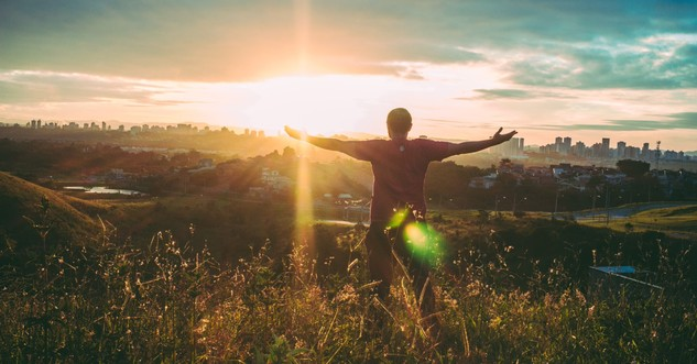 Man facing sunrise with arms out