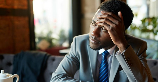 businessman in suite holding forehead and looking wistfully off toward windows in cafe