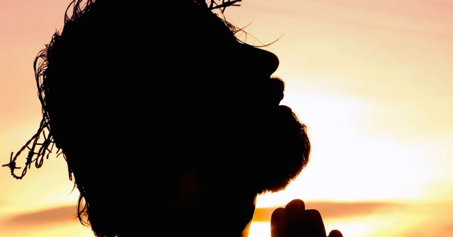 silhouette of man with crown of thorns on head, looking up, praying
