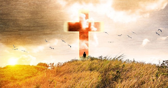man standing in front of a huge cross in a field, you can never lose your salvation