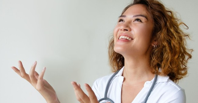 woman looking up an smiling, hands open as if talking happily and casually with God