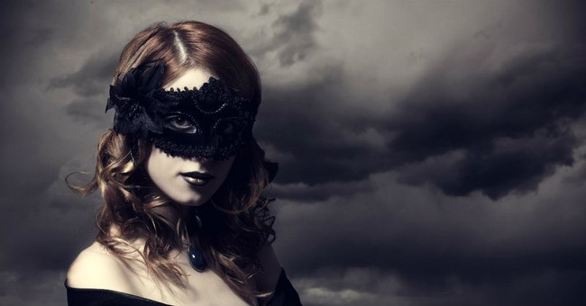 woman in seductive halloween blackbird feather mask cloudy sky