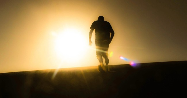 rear view of silhouette man running up hill toward sunset