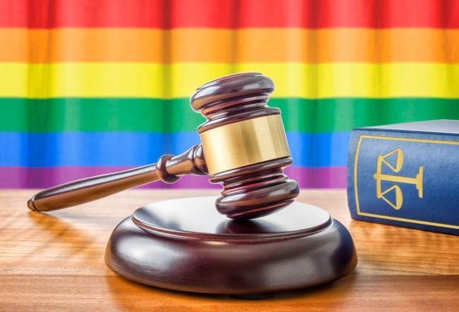 gay rainbow flag behind judge gavel and law book