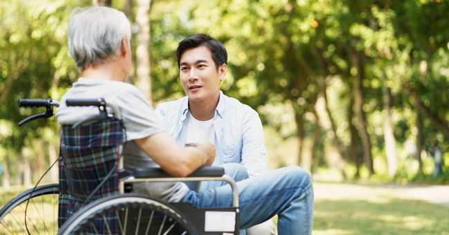man kneeling down to have conversation with senior in wheelchair
