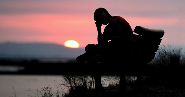 young person sitting on a bench at sunset looking tired and discouraged, prayer when faith is tired
