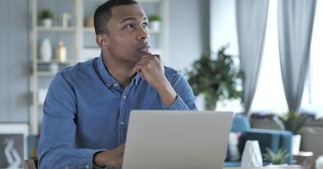 man looking up and off to right in deep thought at laptop