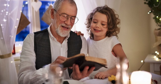 senior man reading Bible with granddaughter with little white lights in background