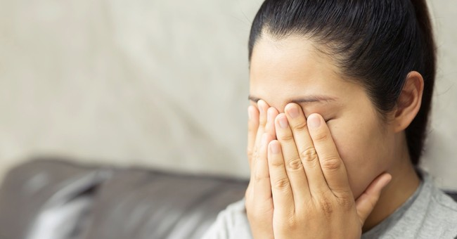 woman covering face sad to see what she is watching