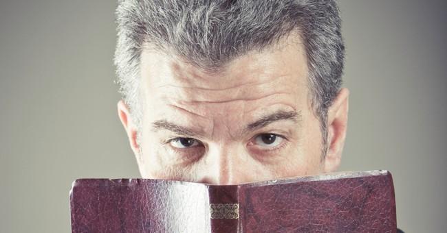 man peering over top of open Bible