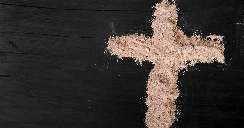 ash Wednesday ashes in shape of cross on table