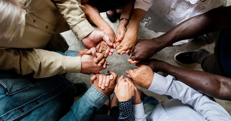 People holding hands in a prayer circle