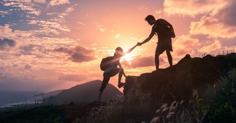 Man helping a woman on a hike - by grace through faith