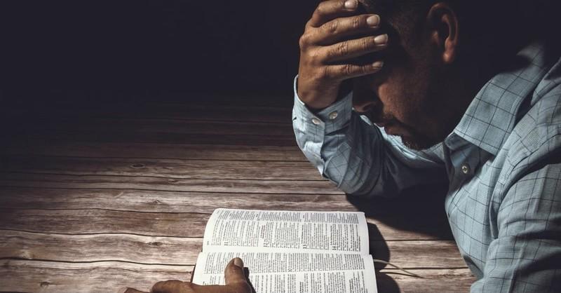 sad man reading Bible, psalms of lament
