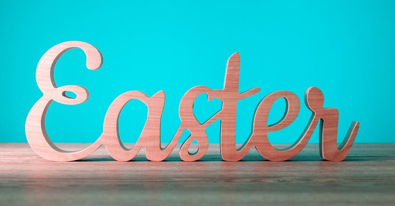 Wooden Easter sign on table with teal background
