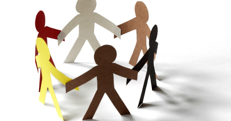 cutout paper people of all skin colors joining hands in a circle racial reconciliation