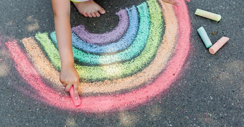 child drawing rainbow chalk on sidewalk street, hope during coronavirus