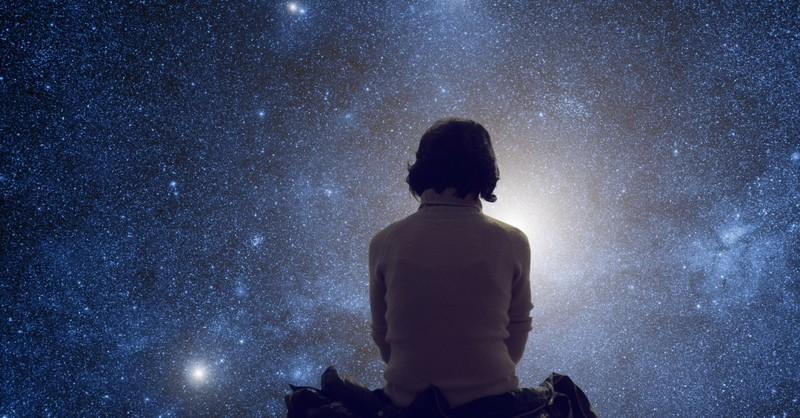 Woman sitting outside in nature looking at starry night sky