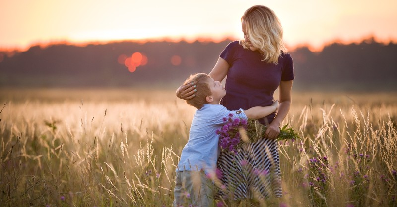 mother hugging young son in a field with flowers