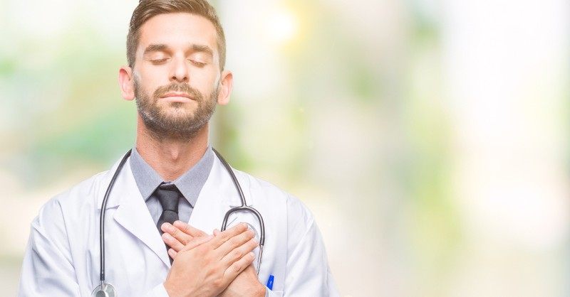 Docteur fermant les yeux dans la prière