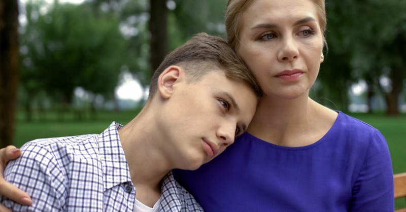 teen boy putting head on mom's shoulder