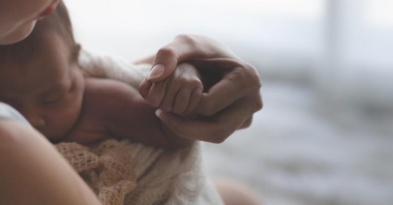 Mom holding newborn hand