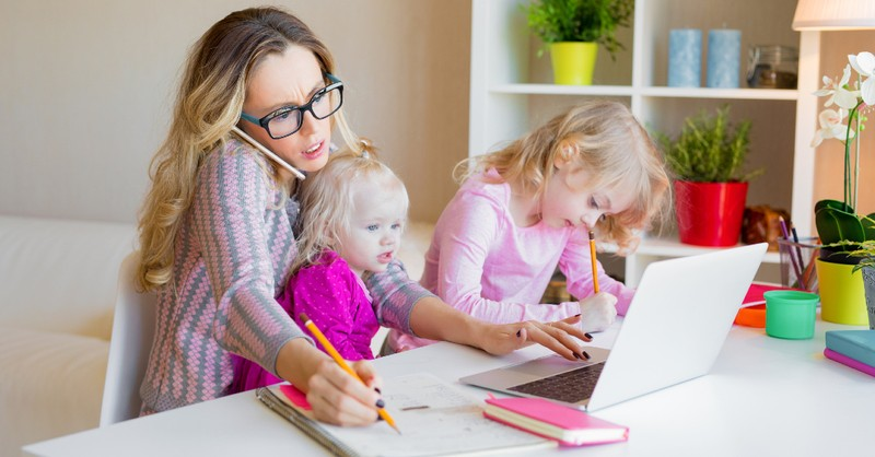 Busy mom working at home with young kids