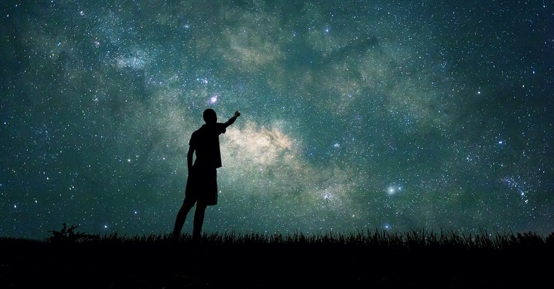 silhouette of man reaching up to stars in the nigh sky