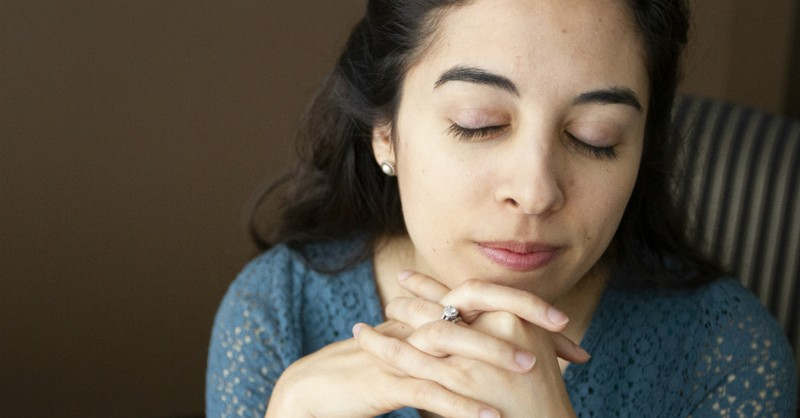 woman praying with hands folded and eyes closed
