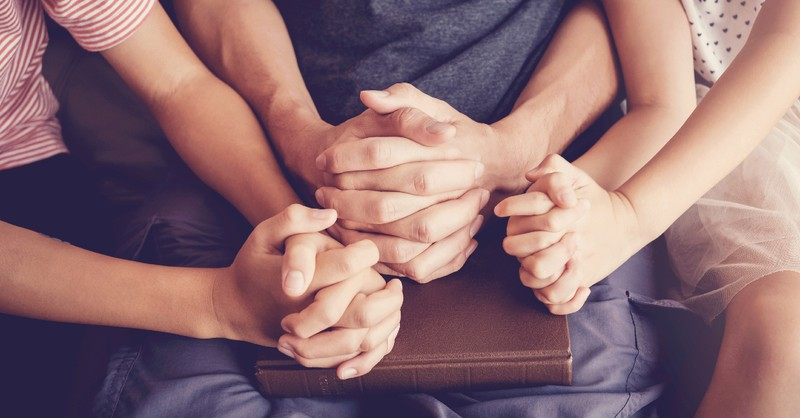 family holding hands over bible