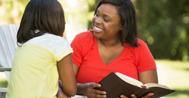 mom outdoors on patio chair reading bible smiling at daughter