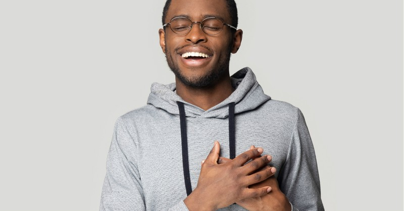 man smiling hands over heart peace and joy