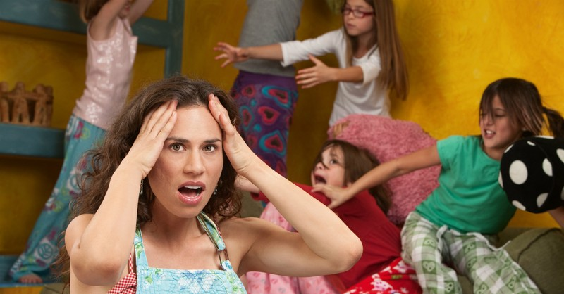 stressed mom with girls play fighting in background