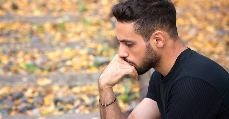 man pensive sad wondering outdoors