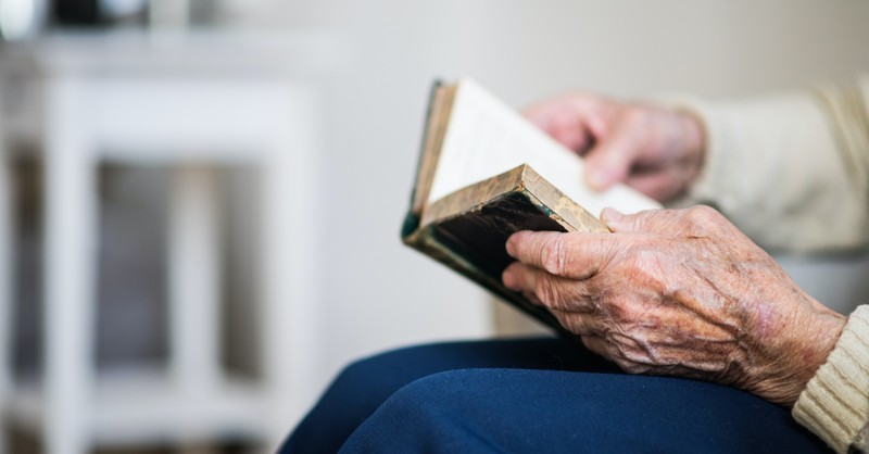 An old person holding a Bible