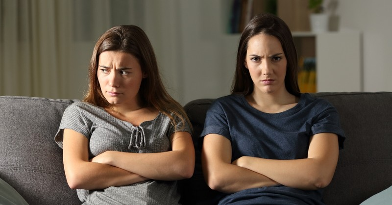 two women sitting on couch with crossed arms looking upset and angry, how to forgive when you don't feel forgiving