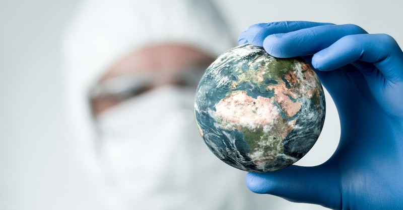 Man in hazard gear holding a globe