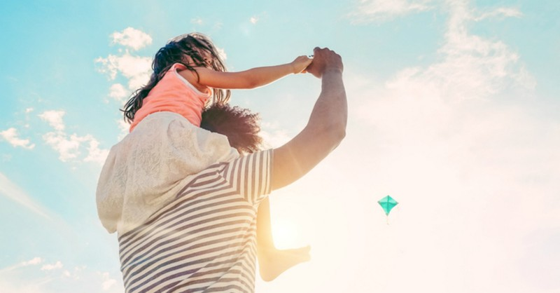 man with daughter on shoulders flying kite blue sky spring