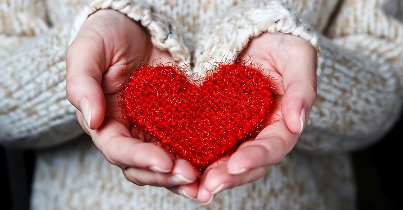 A woman holding a fabric heart, Why generosity is the ultimate form of worship