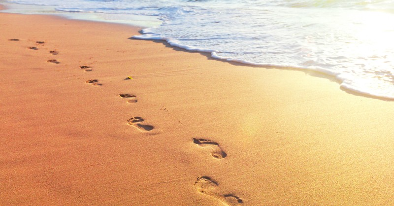 footprints in sand along surf edge