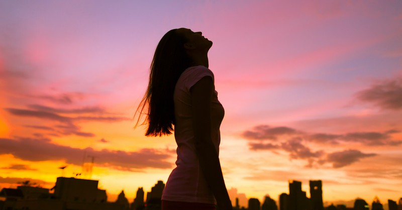 silhouette of woman looking up at sky during sunset against city scape