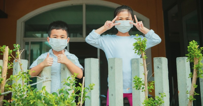 two children waving from house wearing masks
