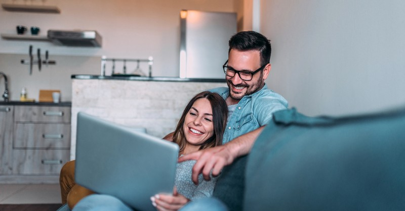 couple happily watching video on laptop together