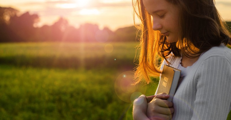 teen holding bible at sunset looking down peacefully