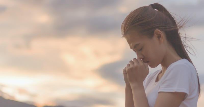 woman praying against sunset background