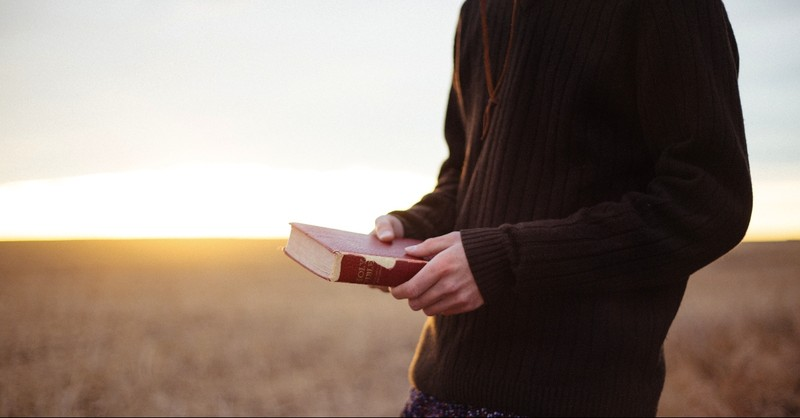 Person standing with the Bible