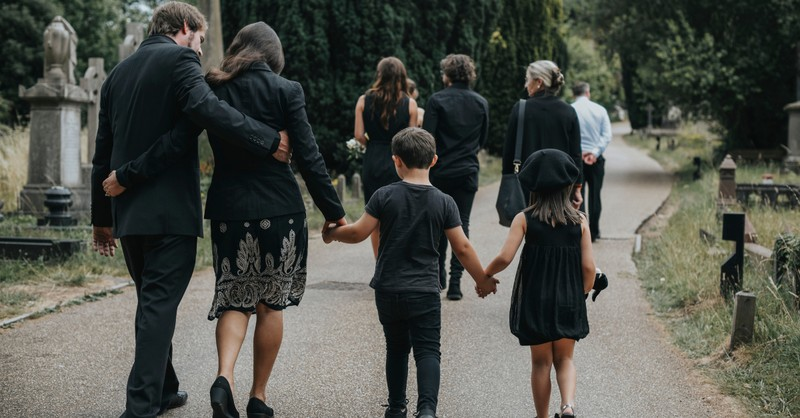 family walking away after funeral in cemetery grieving