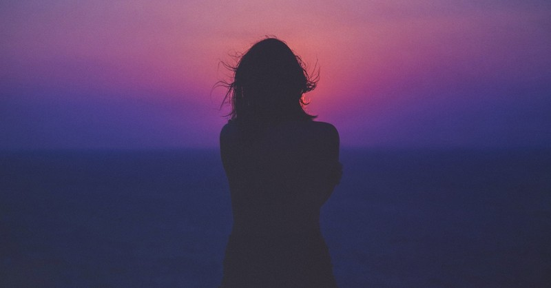 woman silhouette standing in front of ocean sunset sunrise, does mental health struggle mean faith is weak