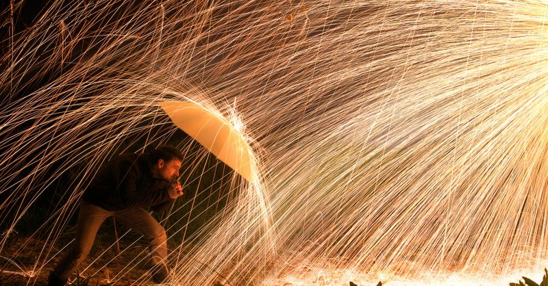 man protecting self from fire sparks with umbrella