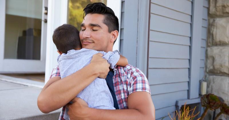 dad hugging toddler son joyful